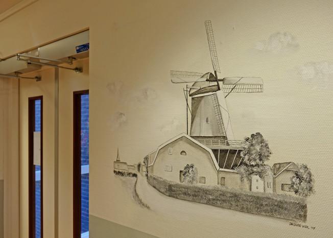 Gang met een afbeelding van een molen op de muur in zorglocatie Elim in Putten